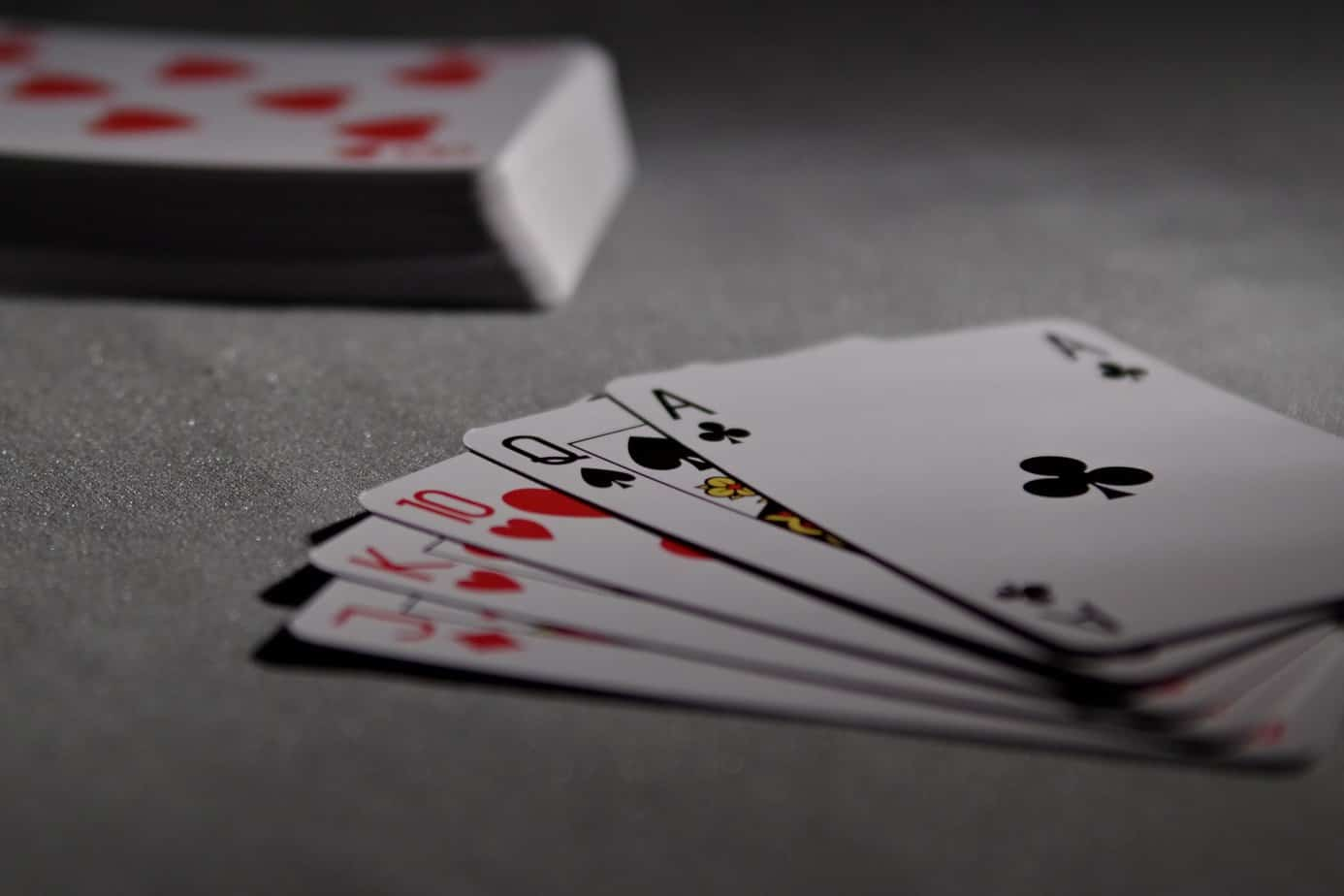 A royal flush in front of a deck of cards