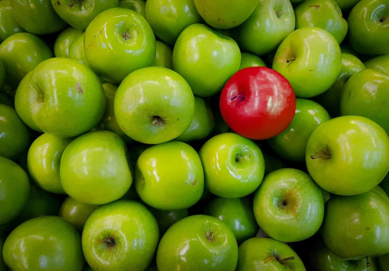 One red apple among many green ones
