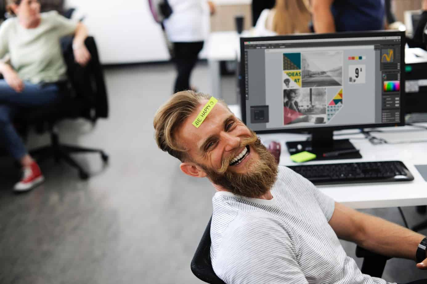Laughing man sitting in front of a computer