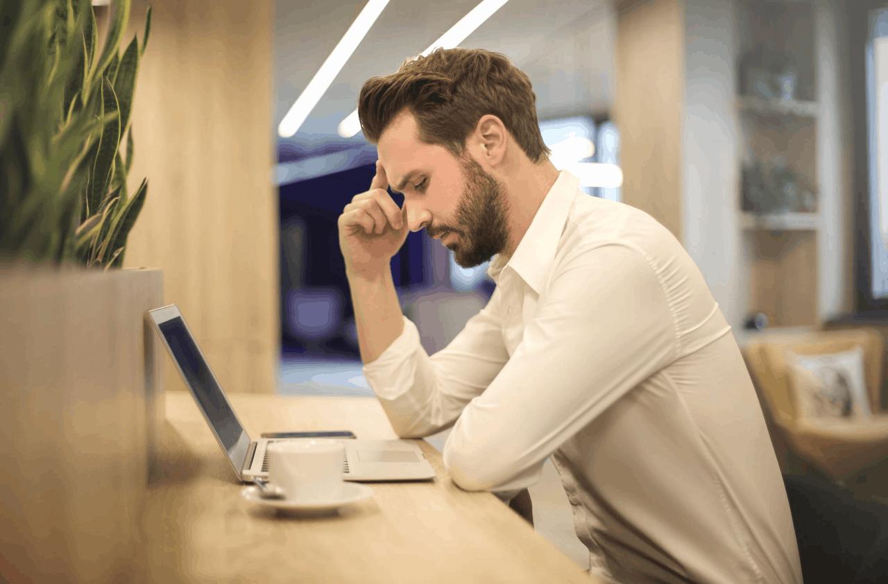 A puzzled man studies his laptop