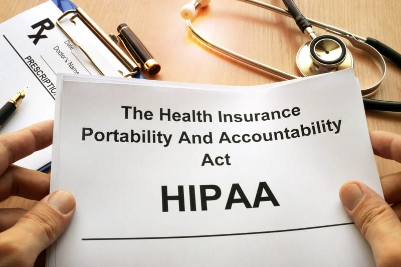 Medical tools on a table with a paper that reads HIPAA