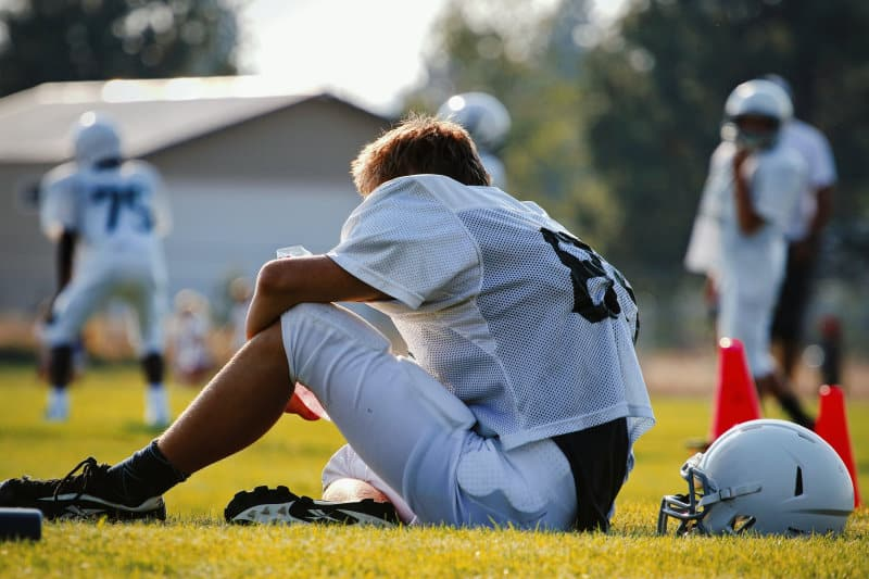 Young football player sits while teammates practice