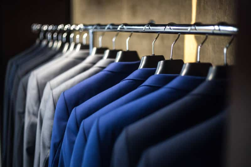 A rack of gray, blue, and black suits