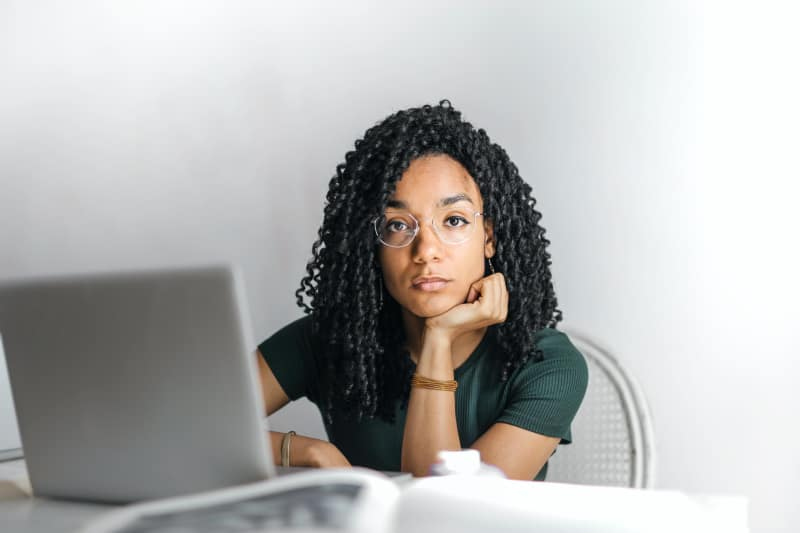 Serious woman with glasses sits in front of laptop and looks into camera