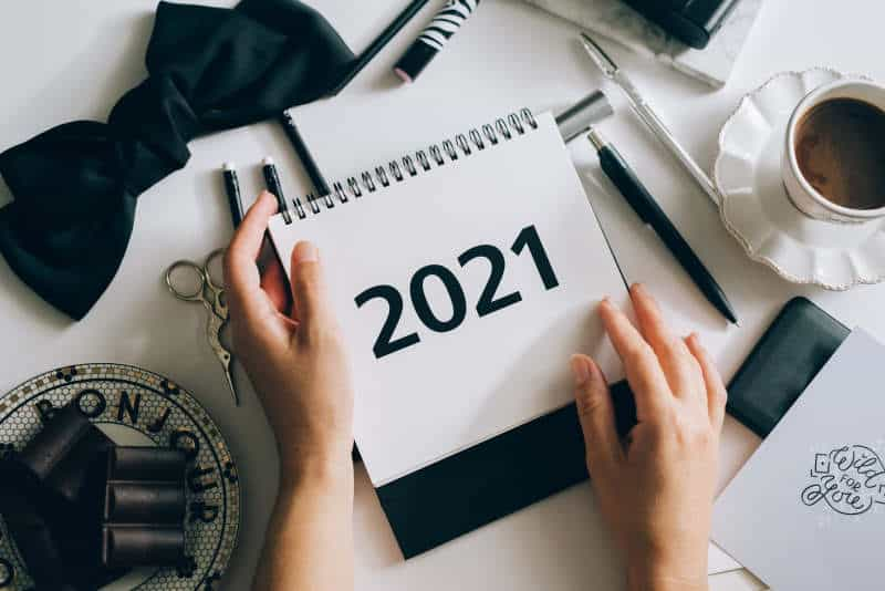 Person planning for 2021 in a notebook