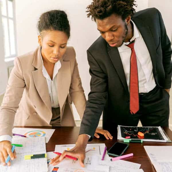 Woman and man in business clothes examine plans