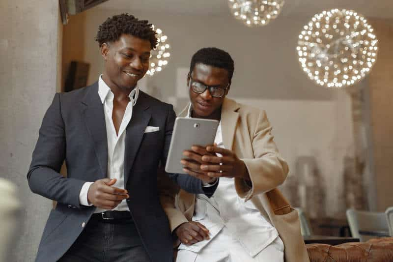 Two businessmen chatting about the contents of a tablet