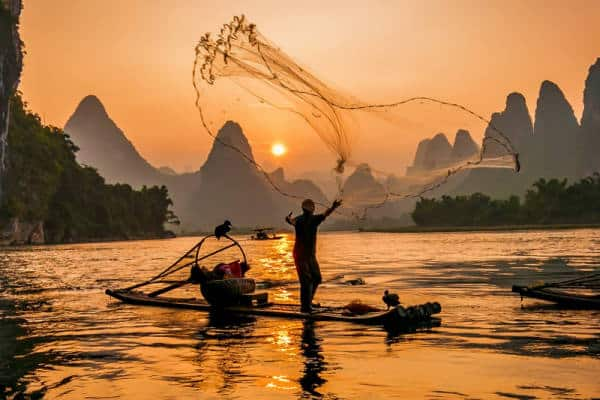 Fisherman on a boat casting a net, much like BDRs contact as many people as possible