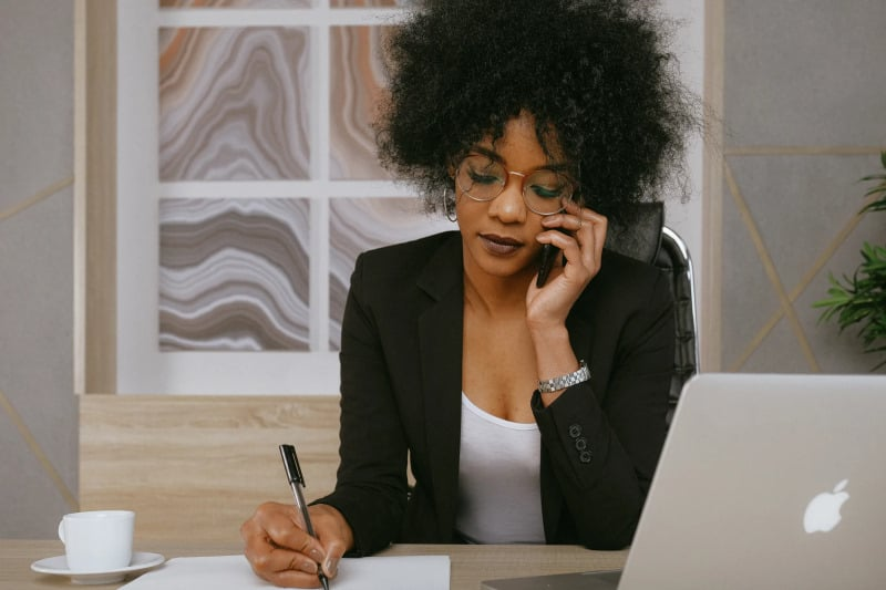 Woman on phone and sitting at desk making decisions