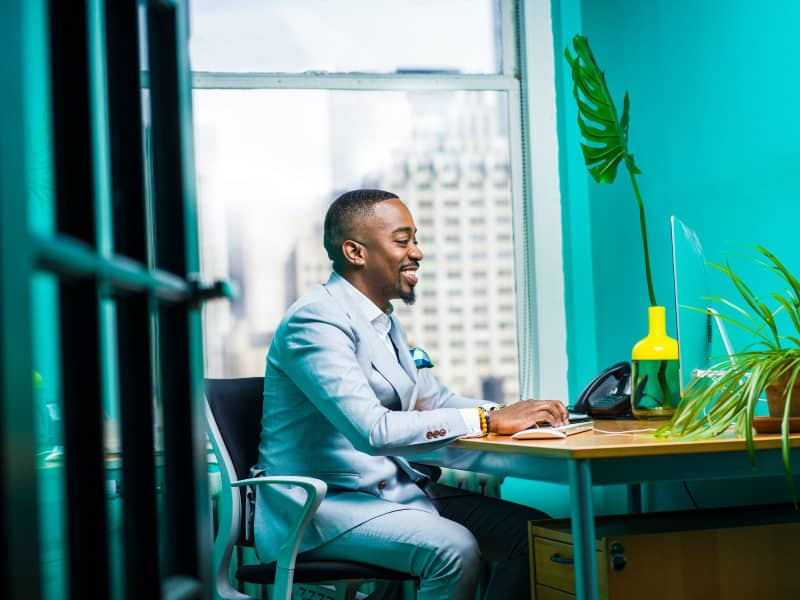 Professional businessman sitting at a desk in a teal room