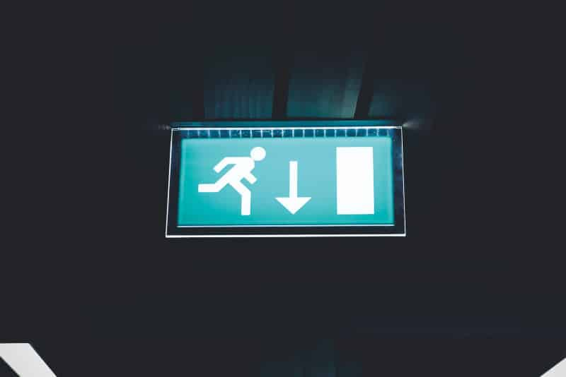 Glowing green exit sign hanging from the ceiling