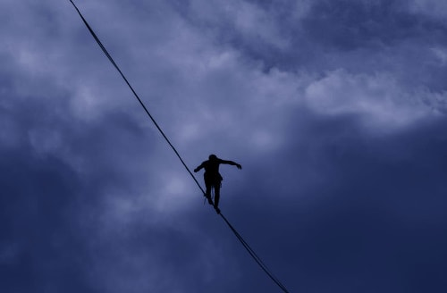 Person walking on a tightrope against a cloudy background
