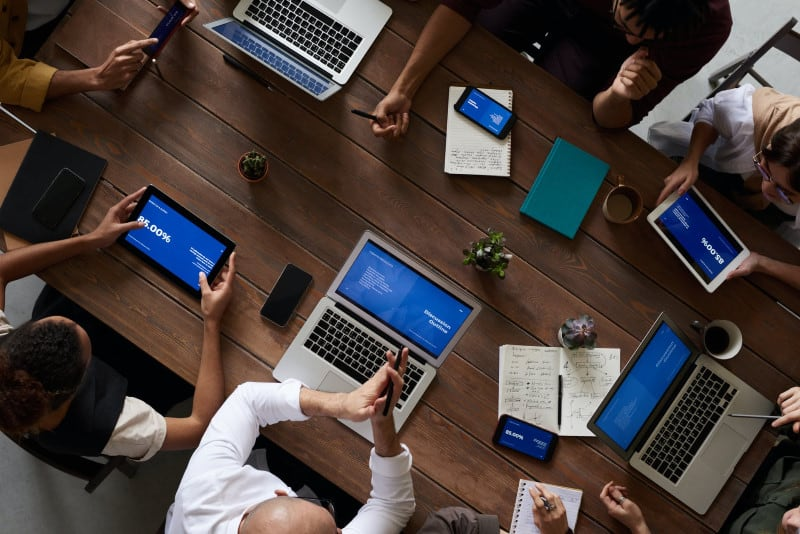 Top view of a group of people with laptops sitting at a table
