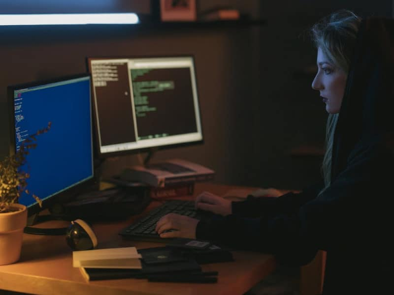 Hooded woman with dual hacking monitors