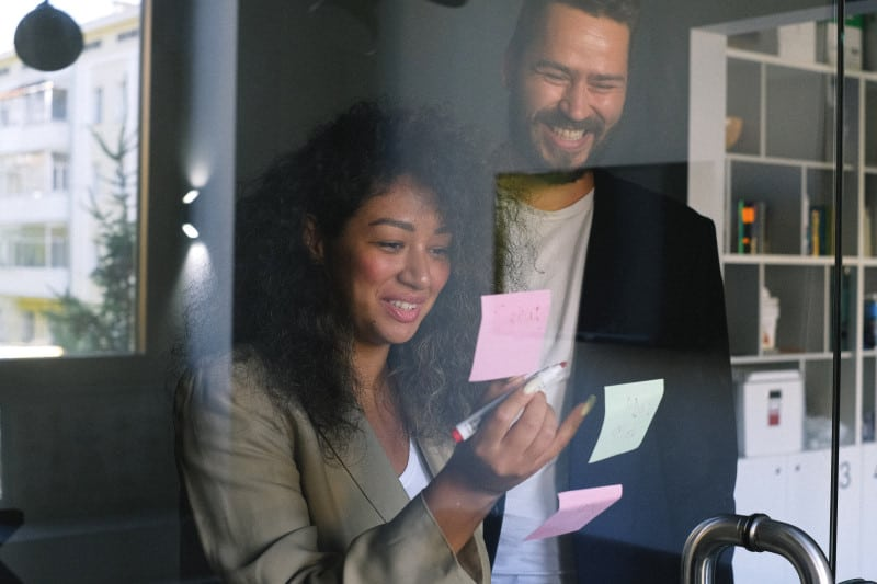Business partners writing on sticky notes