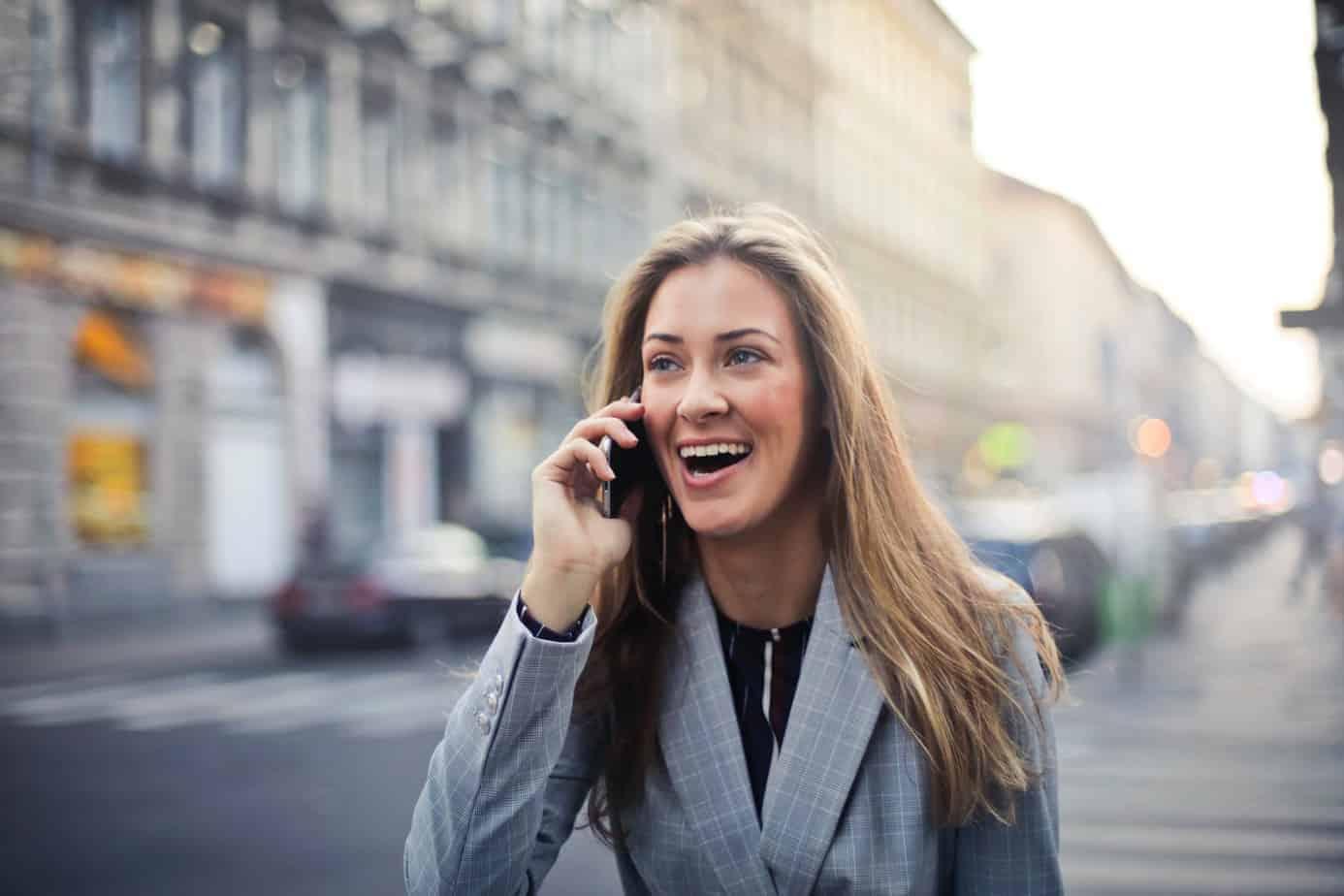 Pleasantly surprised blonde woman on phone