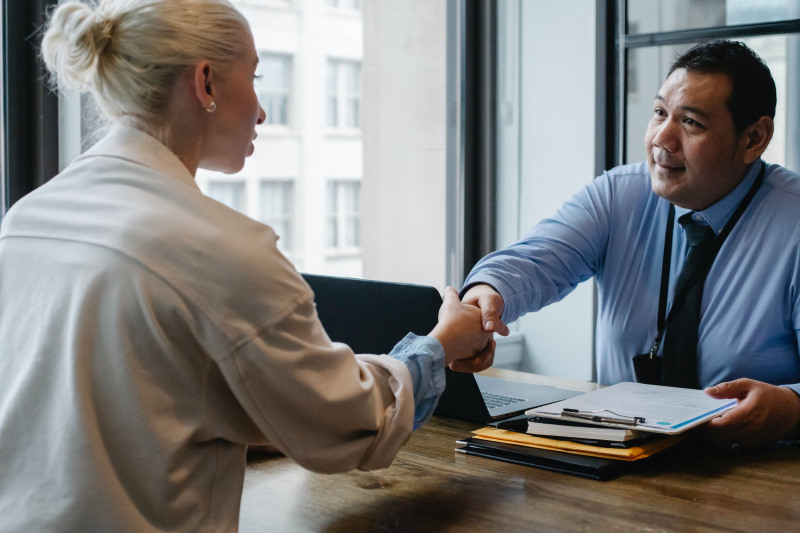 Two people in business attire shake hands over a table