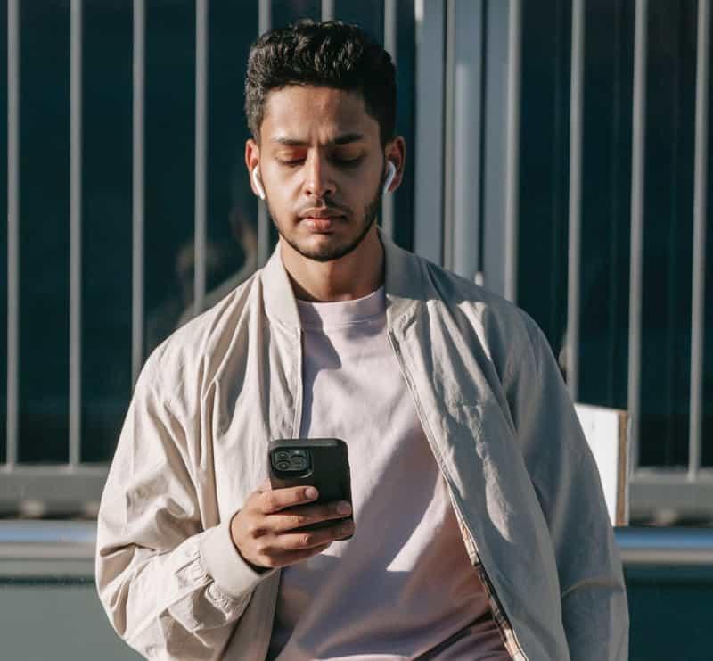 Man checks his phone while outside