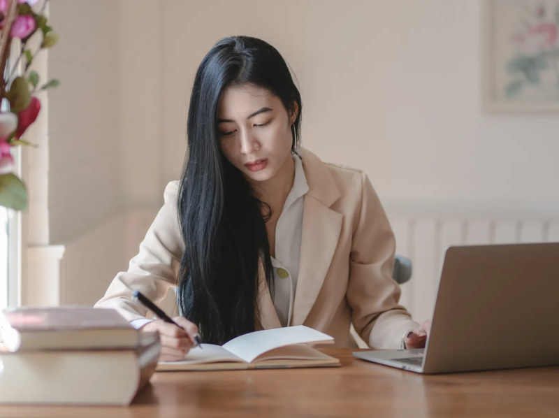 Woman sits at desk in front of a notebook and a laptop